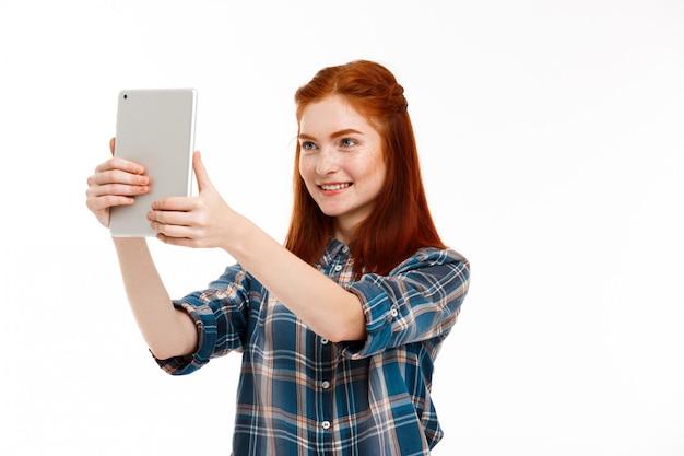 Belle gingembre faisant selfie sur mur blanc.