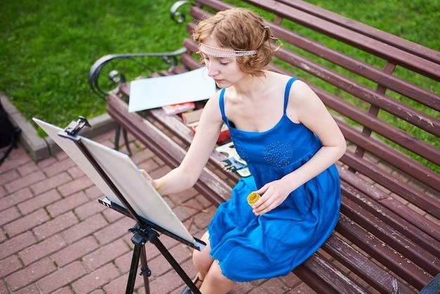 Belle girlartiste dans la rue dans une robe bleue s'appuie sur le chevalet