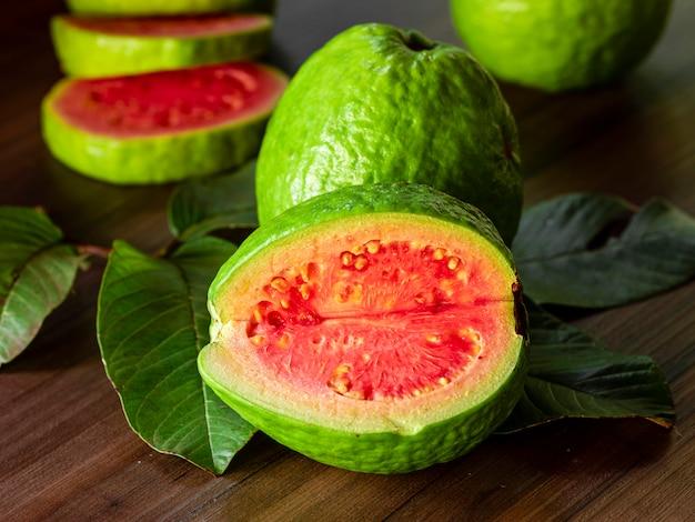 Belle goyave rouge fraîche, fruits d'automne sur fond rustique en bois