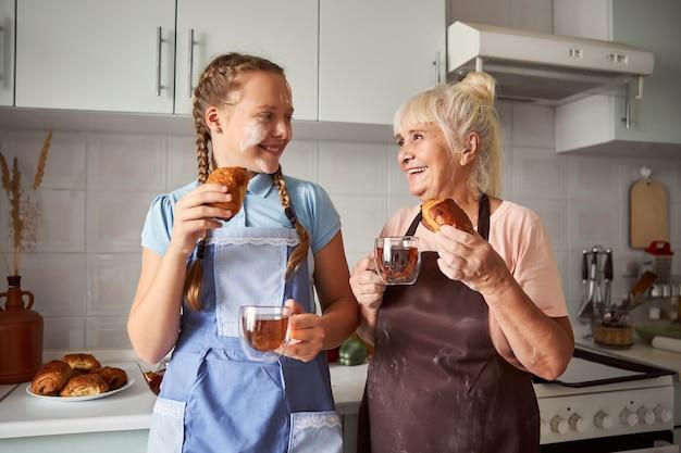 Belle grand-mère dégustant des pâtisseries faites avec sa petite-fille