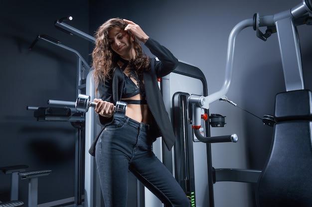 Belle grande femme aux cheveux bruns dans un costume posant dans la salle de gym avec un haltère