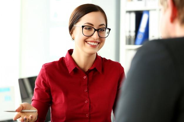 Belle greffière souriante portant des lunettes avec un stylo argenté