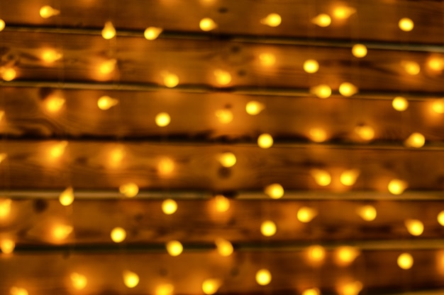 Belle guirlande accrochée au mur en bois, flou artistique, bokeh, décor de noël lumineux.