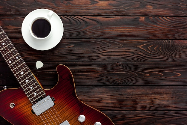 Belle guitare électrique avec un casque et un bureau de café