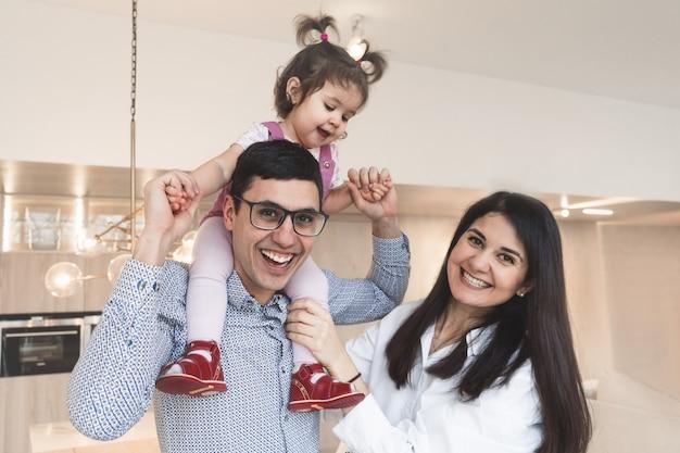 Une belle et heureuse famille se tient dans la cuisine. portrait d'une famille internationale.