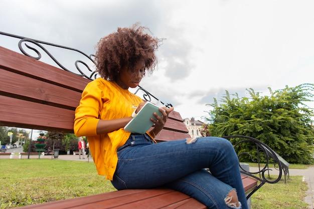 La belle et heureuse femme afro-américaine dans le parc, prend des notes dans un cahier