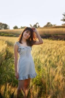Belle et heureuse femme asiatique, profitant de la vie dans le champ d'orge au coucher du soleil.