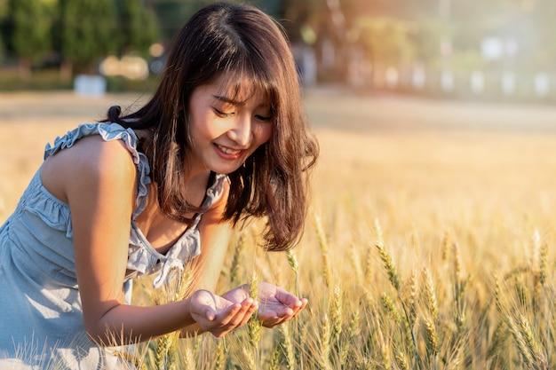 Belle et heureuse femme asiatique profitant de la vie dans le champ d'orge au coucher du soleil.