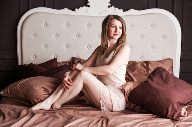 Belle et heureuse femme aux cheveux brun clair dans une chemise beige pose pour la caméra dans sa chambre sur le lit