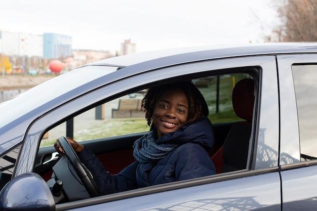 La belle et heureuse femme dans la voiture