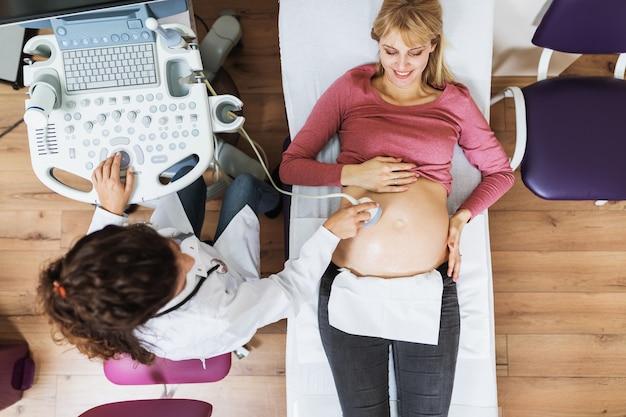 Belle et heureuse future mère lors d'un examen gynécologique avec un équipement médical à ultrasons.