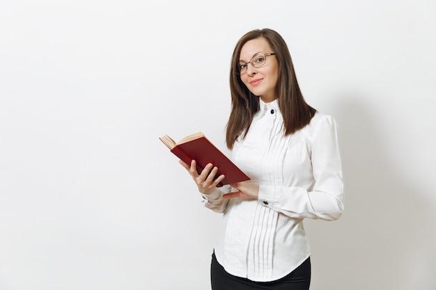 Belle heureuse jeune femme d'affaires aux cheveux bruns souriante en chemise blanche jupe noire lunettes de lecture livre isolé sur mur blanc