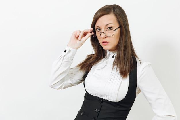 Belle heureuse jeune femme d'affaires aux cheveux bruns souriante en costume noir, chemise blanche et lunettes à la recherche d'une caméra isolée sur un mur blanc