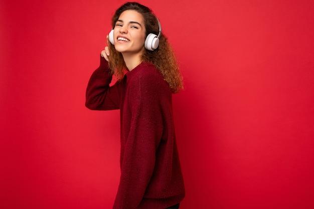 Belle heureuse jeune femme brune frisée souriante portant un pull rouge foncé isolé sur rouge