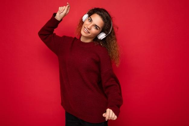 Belle heureuse jeune femme brune frisée souriante portant un pull rouge foncé