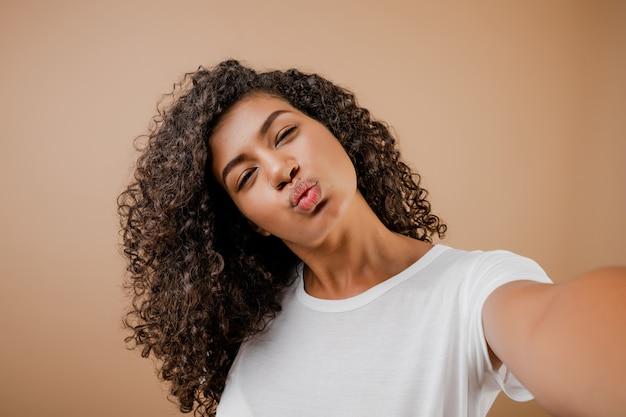 Belle heureuse jeune femme noire faisant selfie isolé sur marron