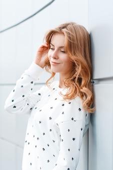 Belle heureuse jeune femme positive avec une coiffure à la mode dans un élégant pull blanc reposant près du mur moderne