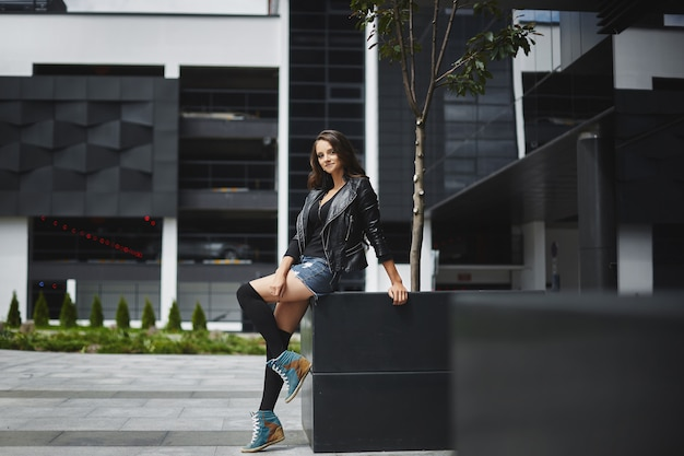 Belle et heureuse jeune mannequin femme dans la veste en cuir noir, short en jean et bas, souriant et posant à l'urbain moderne