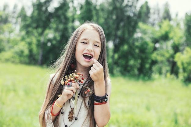 Belle et heureuse petite fille dans la nature avec les fraises dans un style hippie journée ensoleillée