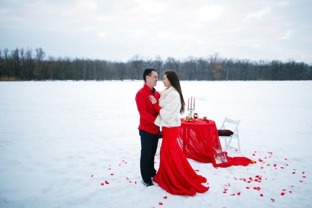Belle histoire d'amour romantique d'amoureux en vêtements rouges posant assis à une table sur un fond de neige