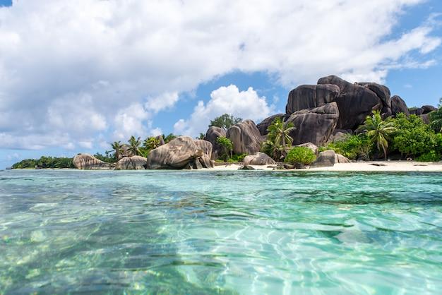 Belle île aux seychelles. la digue, plage de l'anse d'argent. l'eau qui coule et les vagues mousse sur un paysage tropical