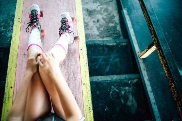 Belle image des jambes de la fille. la fille est assise sur du béton et se repose. elle tient ses genoux ensemble et sa main gauche sur le genou gauche.