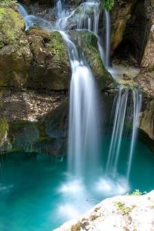 Belle image d'un ruisseau flou de cascades tombant sur des rochers moussus dans une piscine d'eau naturelle turquoise.