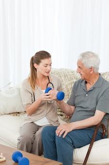 Belle infirmière aidant son patient à faire des exercices