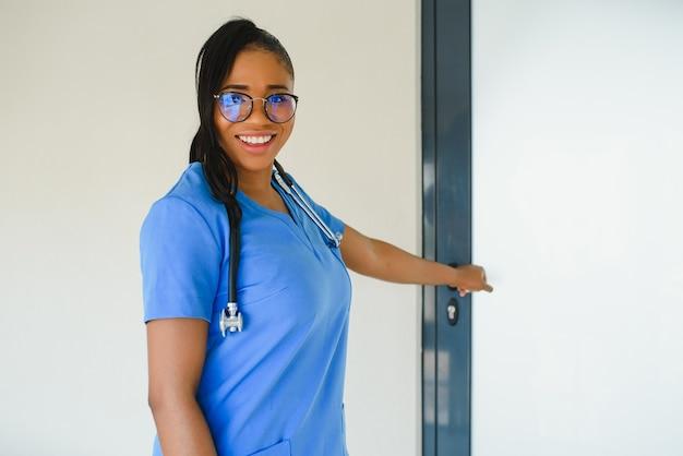 Belle infirmière pédiatrique afro-américaine dans un bureau moderne