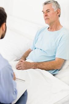 Belle infirmière visitant un homme mûr dans la chambre