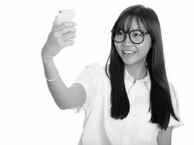 Belle jeune adolescente asiatique isolée contre le mur blanc en noir et blanc