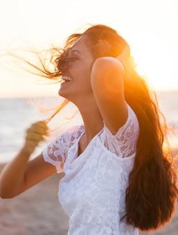 Belle jeune adolescente avec une robe blanche sur la plage au coucher du soleil