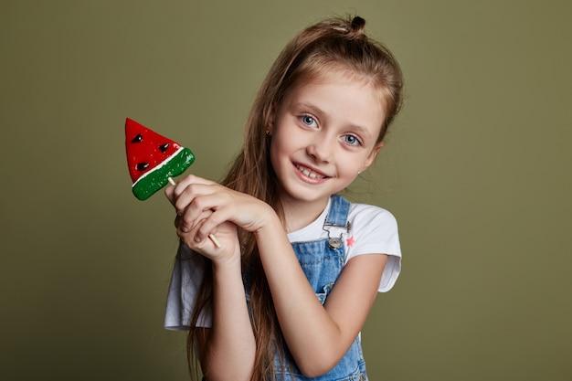 Belle jeune adolescente souriante tenant lollipop