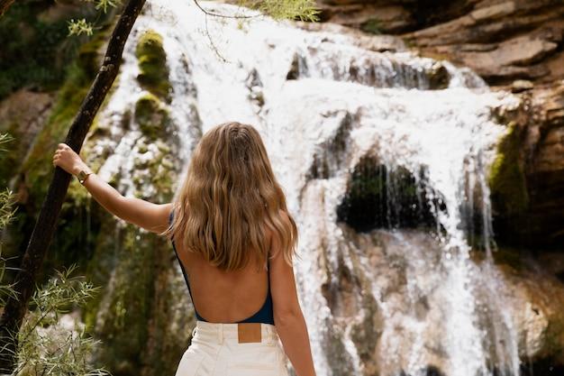 Belle jeune adulte au bord de la cascade