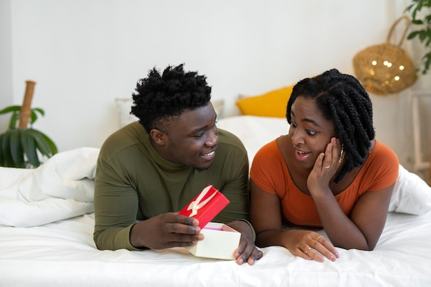Belle jeune africaine au lit avec un cadeau
