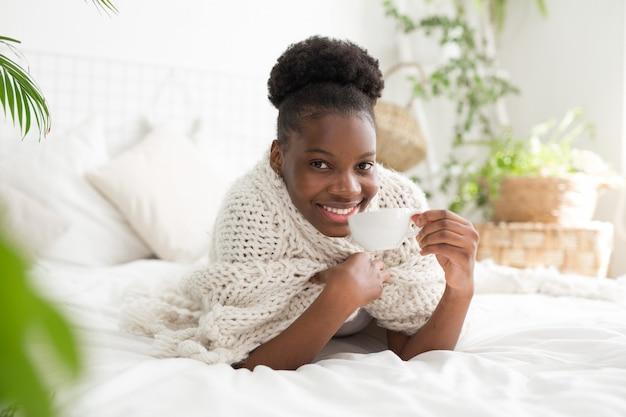 Belle jeune africaine se trouve sur le lit sous les couvertures