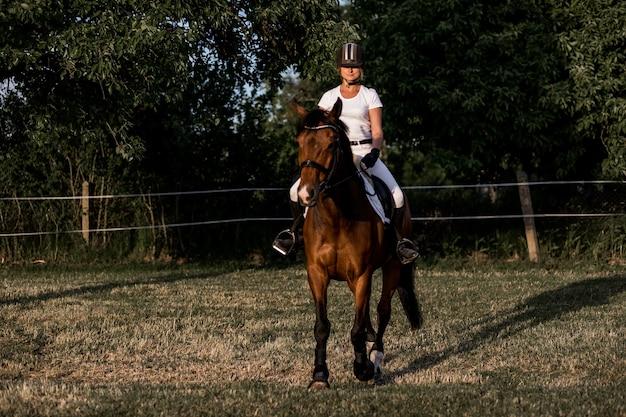 Belle jeune athlète en casque et uniformes de sport blancs s'entraînent par une chaude soirée d'été.