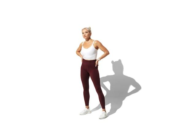 Belle Jeune Athlète Féminine Pratiquant Sur Un Mur De Studio Blanc, Portrait Avec Ombre. Photo gratuit