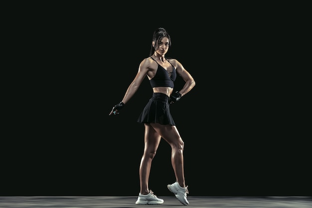 Belle jeune athlète féminine pratiquant sur le noir
