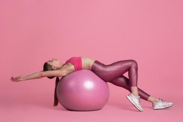 Belle jeune athlète pratiquant sur le portrait monochrome de mur de studio rose