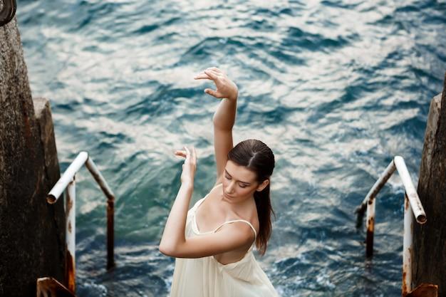 Belle jeune ballerine dansant et posant à l'extérieur