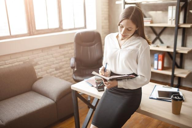 Belle jeune belle femme d'affaires maigre à table dans la chambre. elle regarde la tablette et sourit. humain calme et paisible.