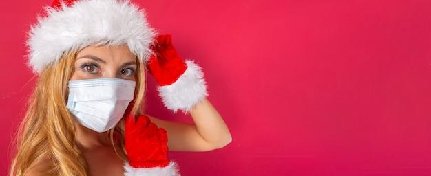 Belle jeune blonde caucasienne avec chapeau de père noël et gants en gros plan avec masque et fond