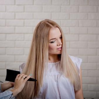 Belle jeune blonde se coiffe après la teinture et le coiffage dans un salon de beauté.