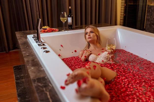 Belle jeune blonde sexy allongée dans une baignoire pleine d'eau et de nombreux pétales rouges frais de fleur rose, boire du vin blanc