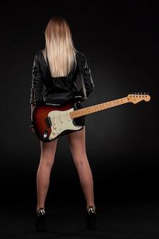 Belle jeune blonde vêtue de cuir noir avec guitare électrique