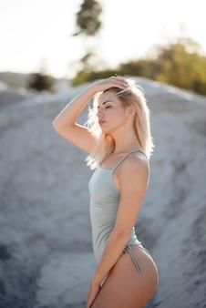 Belle jeune blonde vêtue d'un maillot de bain tendance debout pendant une chaude journée d'été à la carrière de sable. mannequin avec un corps mince et sexy posant à l'air frais.