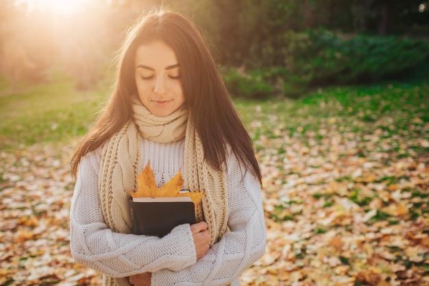 Belle jeune brune assise sur une feuille d'automne tombée dans un parc, lisant un livre.