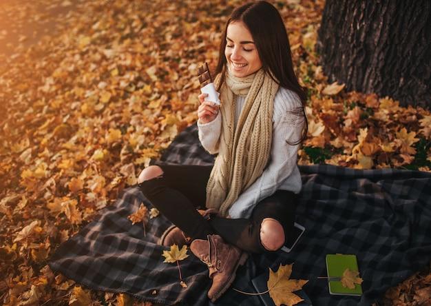 Belle jeune brune assise sur une feuille d'automne tombée dans un parc