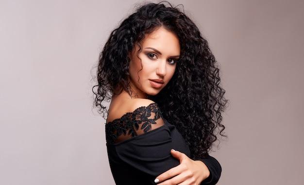 Belle jeune brune aux cheveux bouclés et maquillage lumineux
